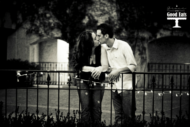 couple kissing against rail with lights strung on it