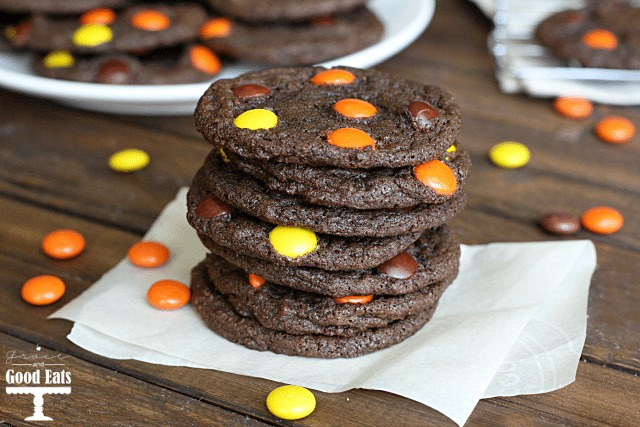 stack of reese's pieces cookies on a piece of parchment paper