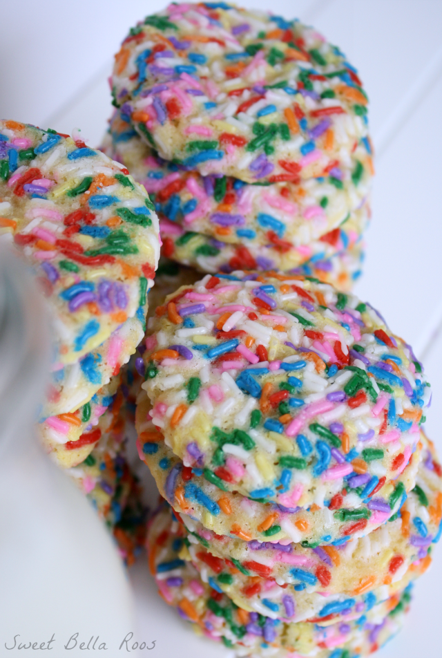 Three tall stacks of confetti cookies next to a pitcher of milk.
