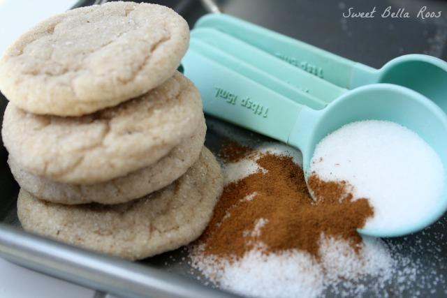 stack of three cinnamon sugar cookies next to cinnamon-sugar mixture and measuring spoons