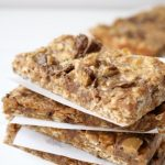 Peanut Butter Cup Granola Bars stacked between parchment paper