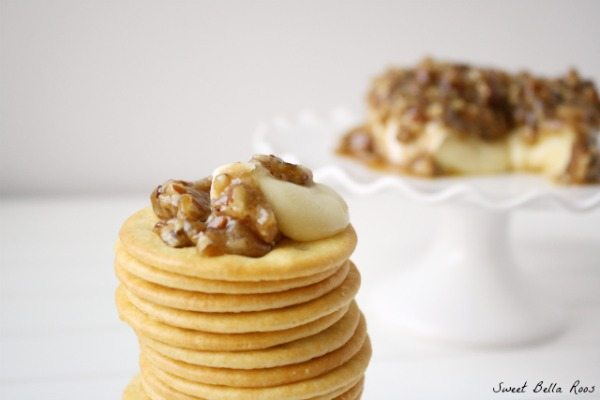 A stack of crackers topped with pecan brie cheese.