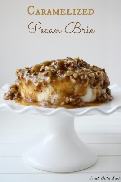 A pecan brie appetizer on a small white cake stand.