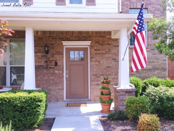 front porch with American flag and vertical planter