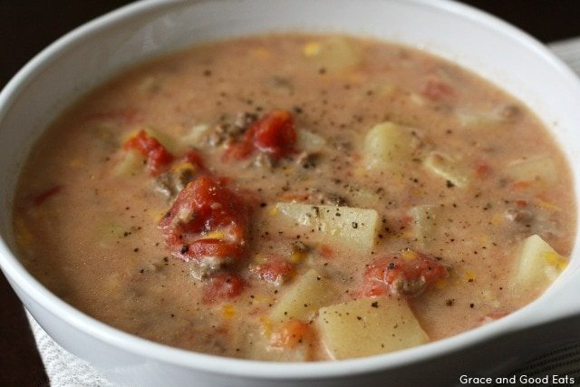 bowl of crockpot cheeseburger soup with chunks of potatoes, ground beef, and diced tomatoes