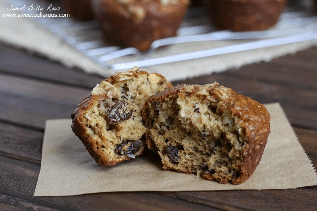 An oatmeal raisin muffin cut in half resting on a square of parchment paper.
