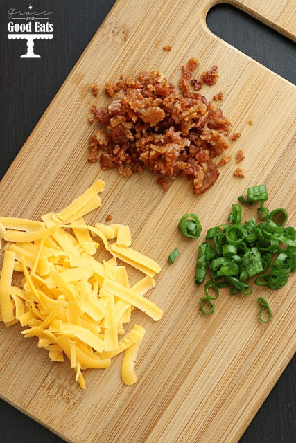 overhead view of crumbled bacon, shredded cheese, and chives on a wood cutting board