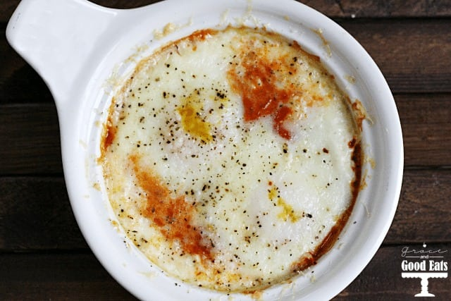overhead shot of a white bowl with eggs, marinara, and cheese