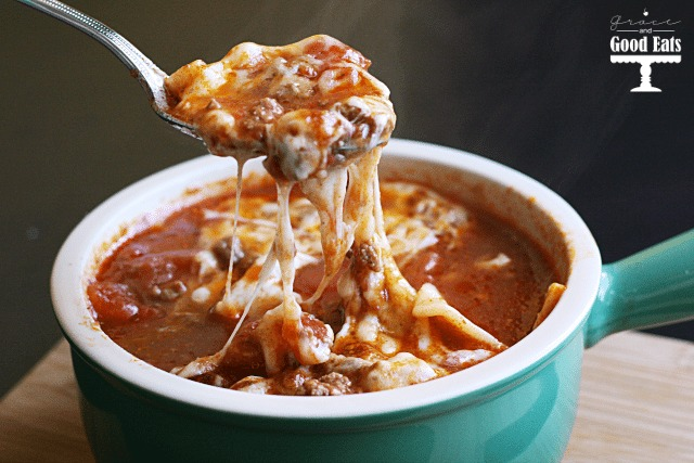 a portion of cheesy lasagna soup being spooned from a soup dish