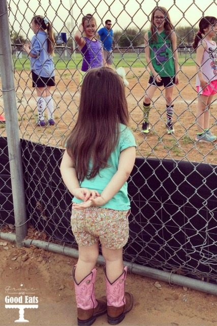 little sister watching big sister play sports