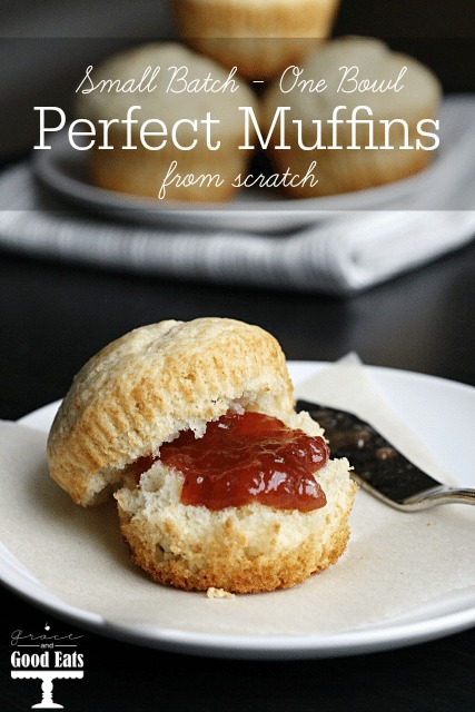 A plain muffin slathered with jam on a white plate.