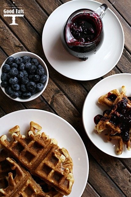 jar of blueberry sauce next to a plate of waffles