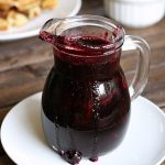 blueberry syrup in a small glass pitcher