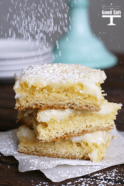 gooey butter bars being dusted with powdered sugar