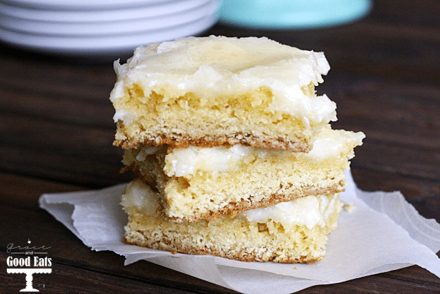 three ooey gooey butter cake bars stacked on squares of parchment paper