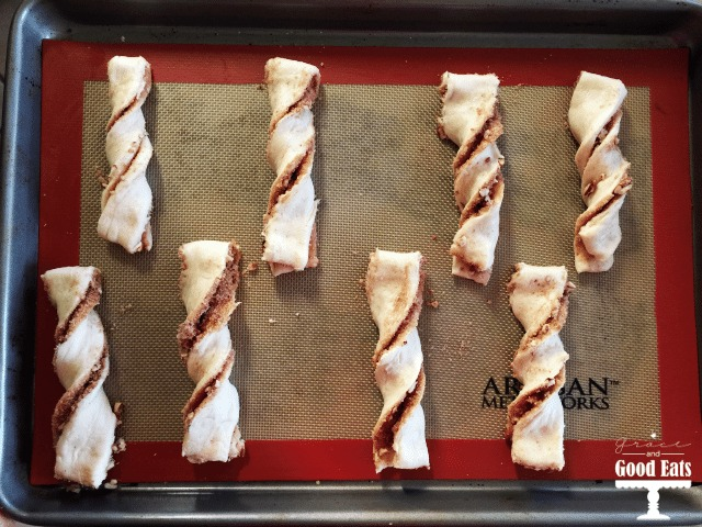 unbaked homemade cinnamon twists on a silpat-lined baking tray