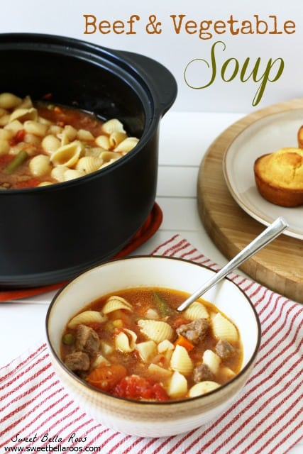 A bowl of beef and vegetable soup. A pot of soup and a plate of cornbread rests in the background.