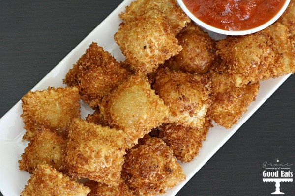 overhead view of fried cheese ravioli on a white tray with a dish of marinara on the side