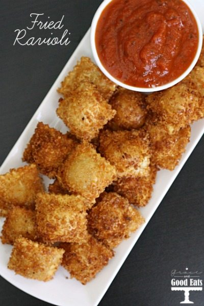 fried ravioli on a white tray with a bowl of marinara sauce