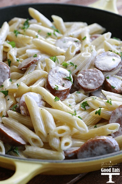 cast iron skillet full of smoked sausage alfredo pasta