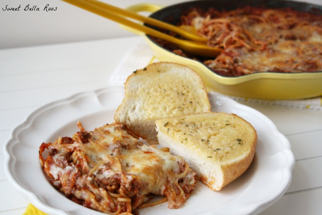 portion of cheesy baked spaghetti with garlic bread on a white plate. A skillet of spaghetti is in the background.