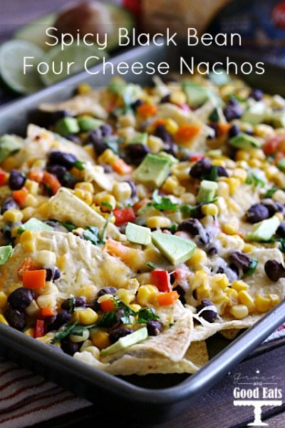 sheet pan full of tortilla chips with black beans, cheese, corn, peppers, and avocados