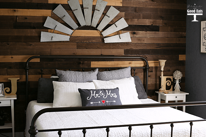 Bedroom inspiration! Love this DIY pallet wall, creamy white bedding, and iron bed!