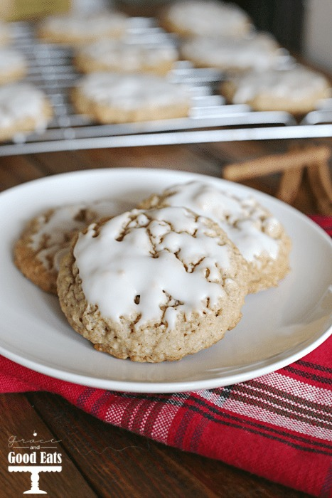 three iced oatmeal cookies on a white plate. A wire rack of cookies sits in the background.
