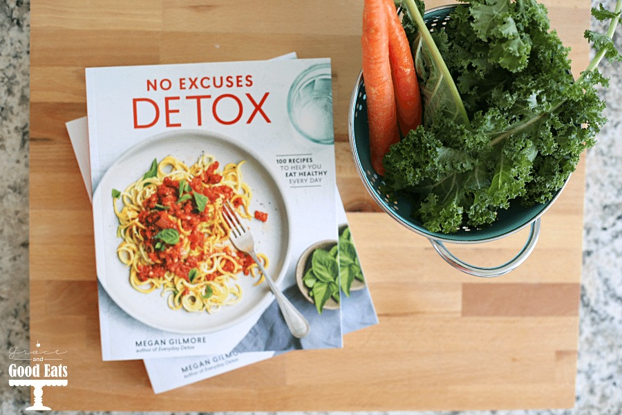 Overhead view of No Excuses Detox cookbook, carrots, and kale.