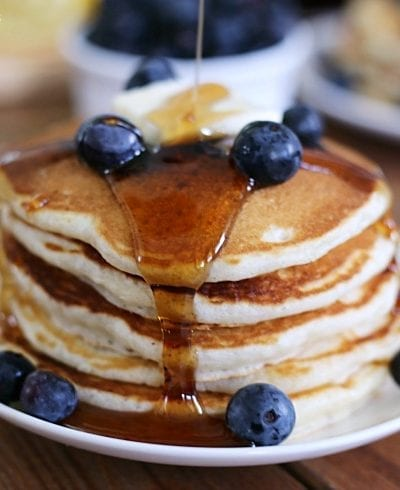 blueberry pancakes topped with butter and syrup