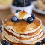 Stack of pancakes with syrup cascading down the sides
