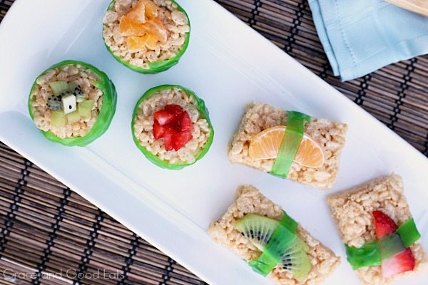 round rice krispie treats on a plate wrapped in fruit leather and topped with fresh kiwi and strawberries