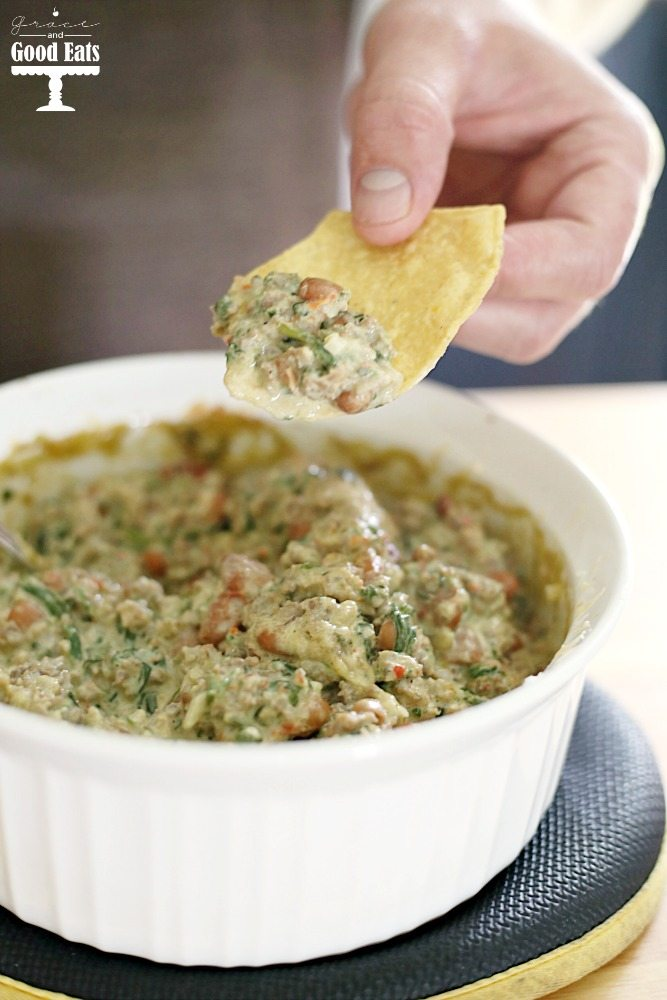 This Sausage and Bean Spinach Dip is a hearty appetizer full of spicy pork sausage and pinto beans. Serve warm for a delicious creamy dip with corn chips, pretzel rods, or bell pepper strips.