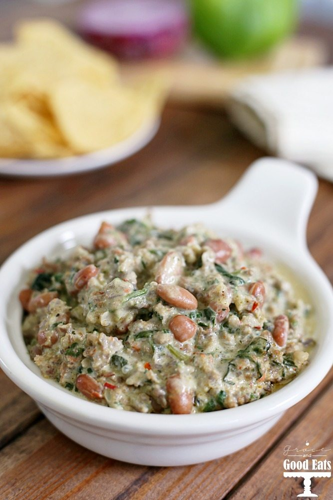 This Spinach, Sausage, and Bean Dip is a hearty appetizer full of spicy pork sausage and pinto beans. Serve warm for a delicious creamy dip with corn chips, pretzel rods, or bell pepper strips.