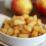 sautéed cinnamon apples in a small white dish with apples and cinnamon in the background