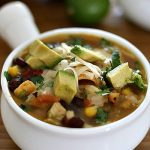 instant pot chicken tortilla soup with beans, corn, chicken, and tomatoes topped with cheese, corn chips, and avocados