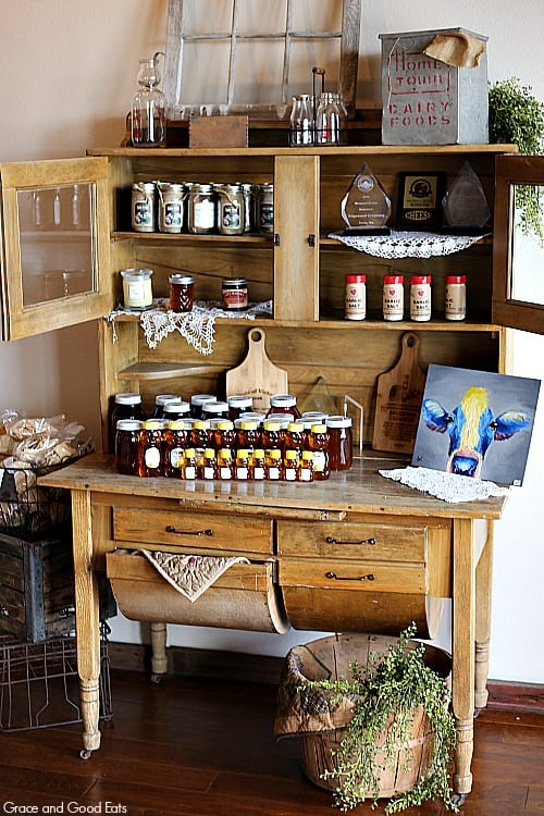wooden hutch filled with goodies for sale like honey, seasonings, and spices