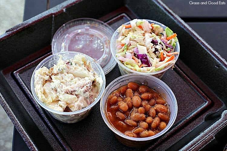 small, clear plastic containers of potato salad, coleslaw, and baked beans