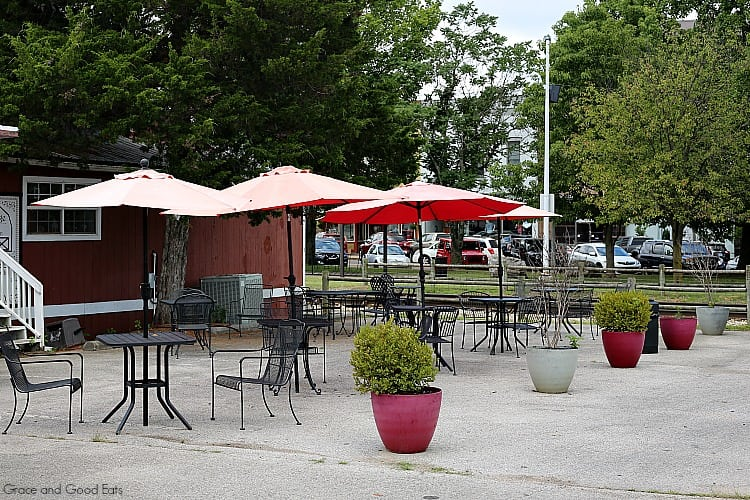outdoor patio tables with red umbrellas surrounded by trees and potted plants