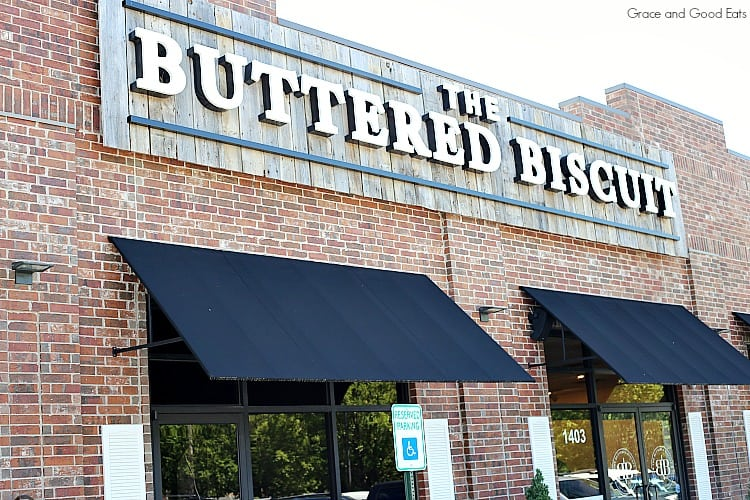 Brick front building with black awnings of The Buttered Biscuit