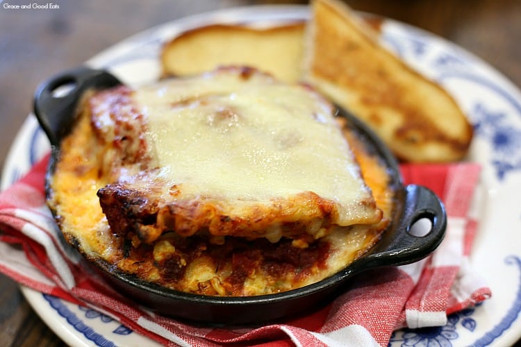 lasagna topped with cheese in a cast iron skillet