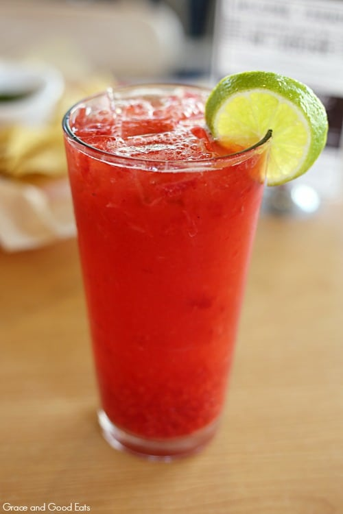 tall glass of red raspberry limeade with a lime wedge