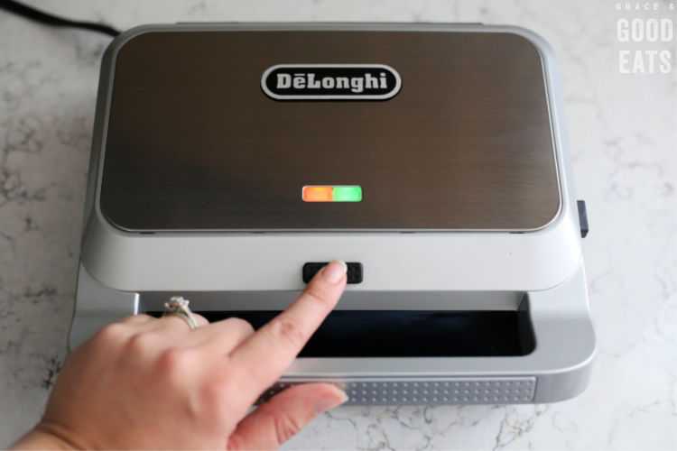pressing the button on a DeLonghi grill