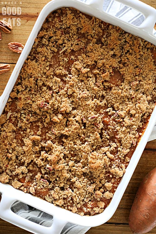 baked sweet potato casserole with pecan topping in a white dish
