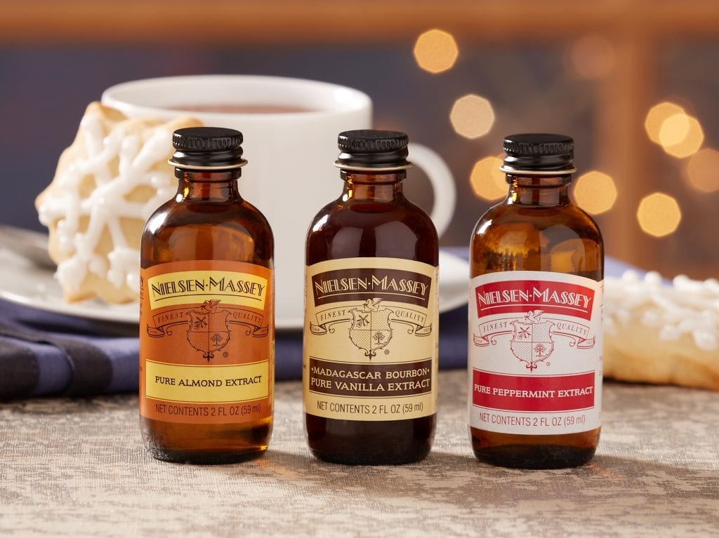 three bottle of Nielsen-Massey extracts in front of a cup of coffee and sugar cookie