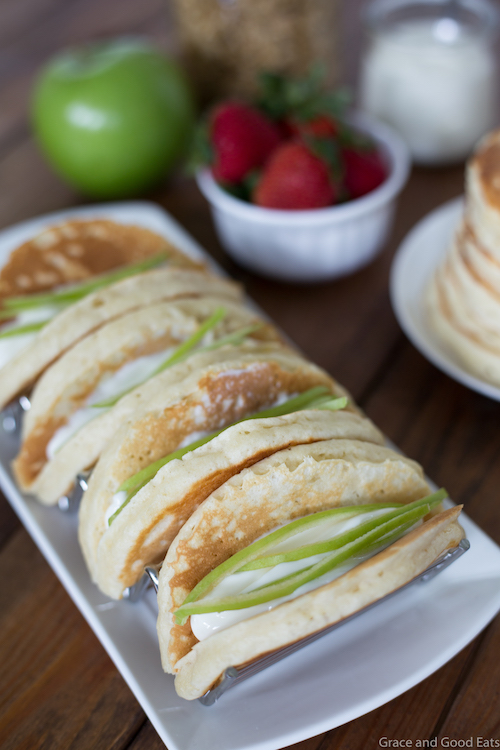 Pancake Parfait Tacos filled with yogurt, granola, apples, and strawberries and topped with a drizzle of honey.  Serve with breakfast potatoes or scrambled eggs for an easy, kid-friendly breakfast!