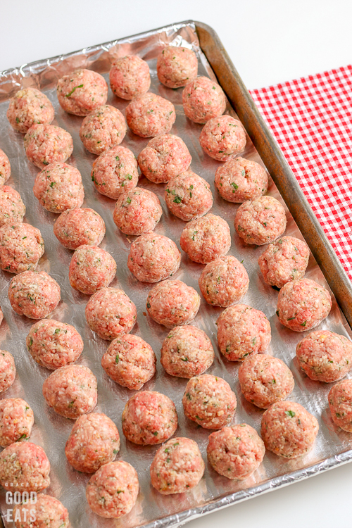 uncooked meatballs shaped into balls on a baking sheet