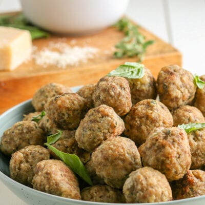 meatballs stacked on a plate topped with basil