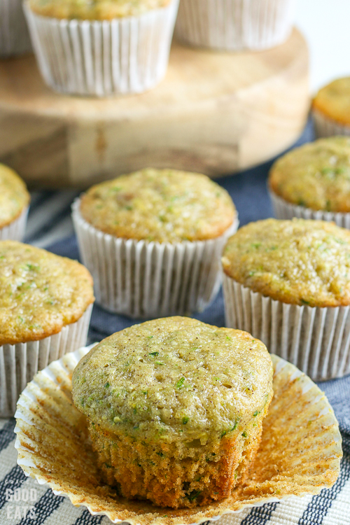 closeup of a zucchini muffin without the liner next to more muffins