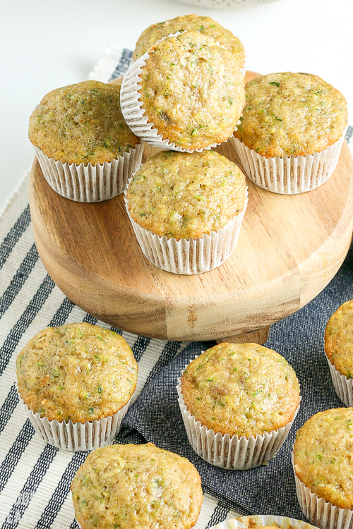 zucchini muffins stacked on a small round cutting board